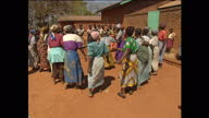 Exterior shots of Malawian women dancing in a circle and singing together on August 12 2002 in Malawi