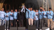 Exterior shots of Manchester City players including Sergio Aguero Joe Hart Vincent Kompany manager Roberto Mancini celebrating with Premier League...