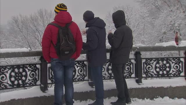 Exterior shots of Mariinsky Park in Kiev winter park scenes Ukrainians Kiev residents people walking in park covered with snow back view Ukrainian...