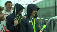Exterior shots of members of Team GB including the Brownlee brothers sheltering from the rain dancing around and waving to crowds from a float during...