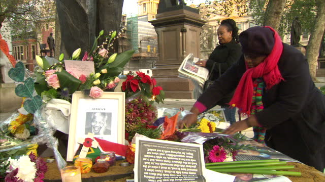 Exterior shots of members of the public lighting candles and looking at tributes laid at the foot of the statue of Nelson Mandela in Parliament...