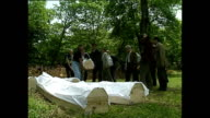 Exterior shots of men digging graves shots of families burying relatives and men chanting prayers next to graves in July 1992 in Sarajevo Bosnia and...
