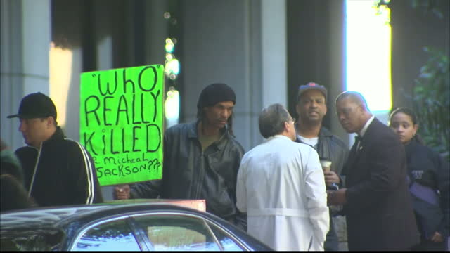 Exterior shots of Michael Jackson fans outside Los Angeles courtroom holding up placards reading 'who really killed Mr Michael Jackson' during the...