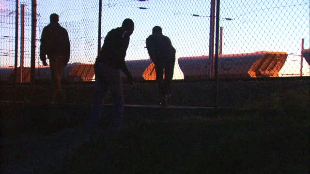 Exterior shots of migrants waiting near railway tracks and sneaking through wire fence and trains passing on August 1 2015 in Calais France
