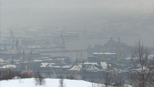 Exterior shots of Murmansk Port with ships moored in snowy icy conditions including Greenpeace's Arctic Sunrise Arctic Sunrise docked in Port of...