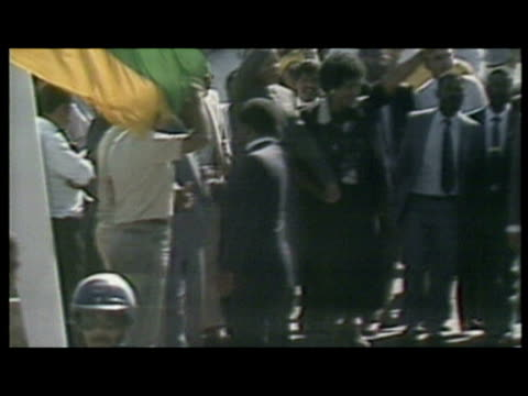 Exterior shots of Nelson Mandela and wife Winnie walking and waving after his release from prison Exterior shots of huge crowd gathered Nelson...