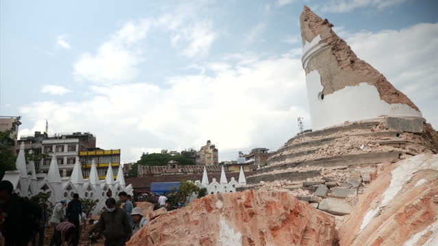 Exterior shots of Nepalese community clearing rubble of the destroyed Dharahara Tower looking for survivors after a major earthquake hit the area...