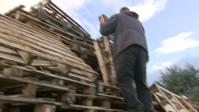 Exterior shots of people building a large bonfire of wooden pallets in preparation for Guy Fawkes Night celebrations on 4 November 2017 in Poynton...