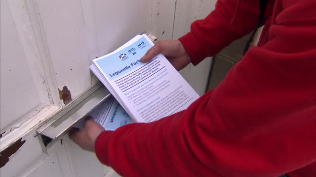 Exterior shots of people delivering Legionnaires' disease advice leaflets through letter boxes of doors on road in Edinburgh for general information...