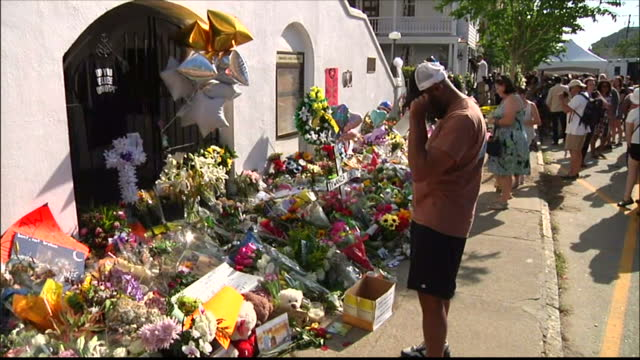 Exterior shots of people gathered outside Emanuel AME Church viewing floral tributes to victims of the fatal shooting attack on a Bible study class>>...