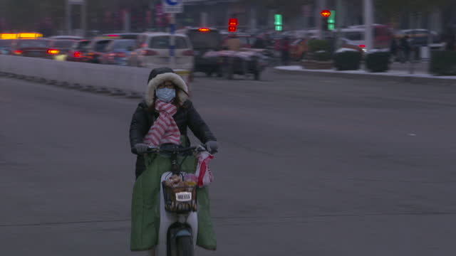 Exterior shots of people in Beijing riding scooters walking and at a bus stop on a smoggy day many wearing face masks on December 01 2015 in Baoding...