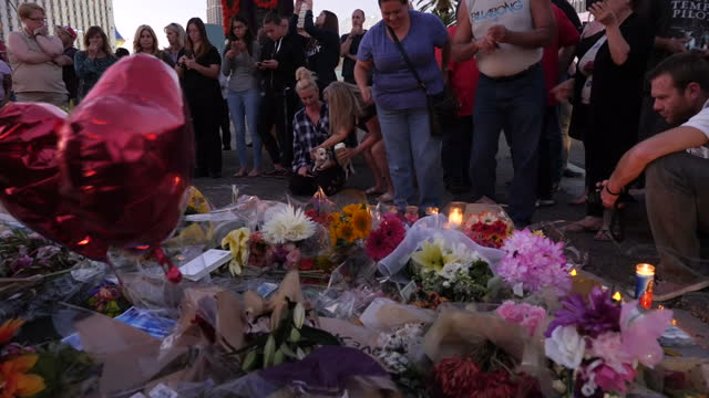Exterior shots of people laying flowers and lighting candles near the scene of the mass shooting by Stephen Paddock on 5 October 2017 in Las Vegas...