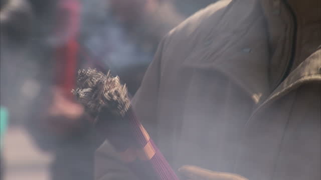 Exterior shots of people praying with incense sticks at The Yonghe Temple also known as the Yonghe Lamasery on March 26 2010 in Beijing China