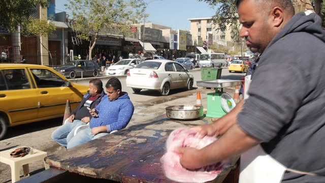Exterior shots of people sat in a case street stall selling doner kebabs a fishmonger gutting a fish and traffic on January 30 2016 in Baghdad Iraq
