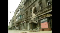 Exterior shots of people sitting in cafes and shots of buildings destroyed from fighting in July 1992 in Sarajevo Bosnia and Herzegovina