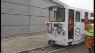Exterior shots of people waiting at the channel tunnel entrance for construction workers to arrive from France in a service train through the tunnel...