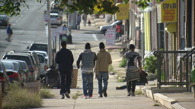 Exterior shots of people walking along pavements and past shops in a blue collar Baltimore neighborhood on November 02 2015 in Baltimore Maryland