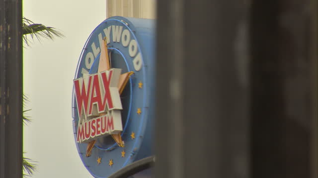 Exterior shots of people walking along the Hollywood Walk of Fame and signs for the Hollywood Wax Museum and Guinness World Records Museum>> on...