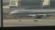 Exterior shots of planes taxiing at Beijing Capital International Airport from the windows of Terminal Three's departures hall including a Boeing 747...