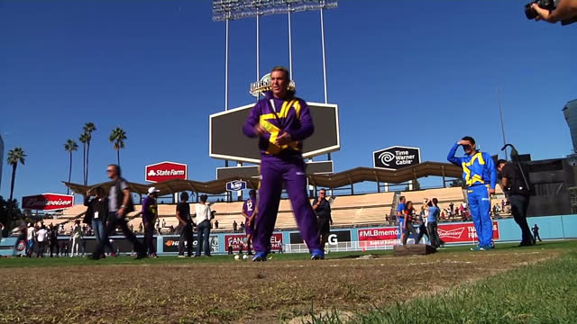 Exterior shots of players of the LA All Stars cricket team training on cricket wicket on the Dodger Stadium pitch bowling balls to young children on...