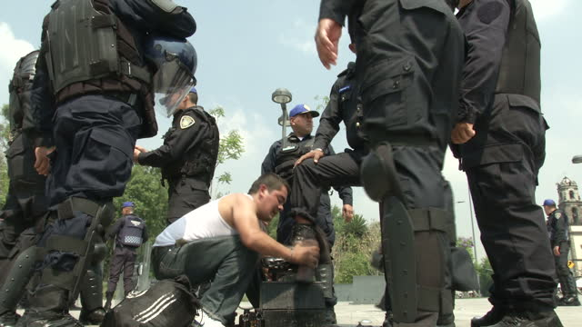 Exterior shots of police in the centre of Mexico City one of whom is having his boots polished by a shoeshine man on June 23 2015 in Mexico City...