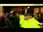 Exterior shots of police mounted and with dogs controlling crowds of riotous football fans