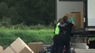 Exterior shots of police officers at the scene where thirteen men and boys were discovered in the back of a lorry at a service station including...