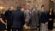 Exterior shots of Prince Charles and Camilla Duchess of Cornwall speaking to members of the Clutha Trust and looking at a ukelele to be auctioned to...