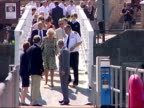 Exterior shots of Prince Charles and Camilla Duchess of Cornwall walking over bridge from promenade towards fishing boats and lifeboats moored in the...