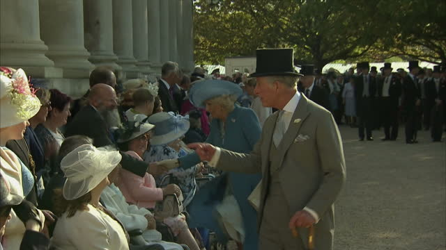 exterior shots of Prince Charles Prince of Wales and Camilla Duchess of Cornwall meeting elderly guests at The Queen's Royal Garden Party at...