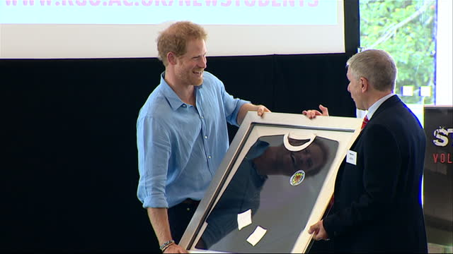 Exterior shots of Prince Harry accepting framed tshirt and walking off stage at the Robert Gordon University on his visit to the Streetsport...
