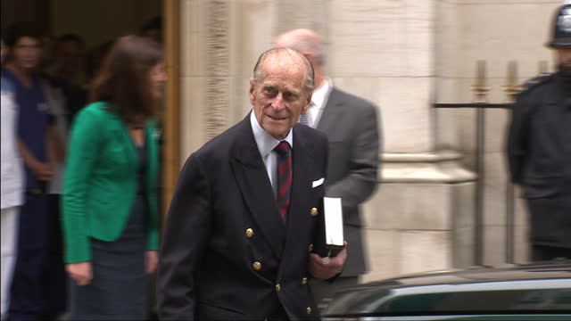 Exterior shots of Prince Philip Duke of Edinburgh shaking hands with hospital staff before leaving The London Clinic getting in a car waving driving...
