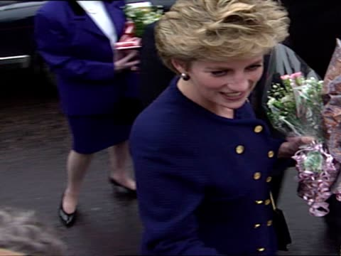 Exterior shots of Princess Diana meeting and speaking with various members of public and being given flowers as she moves along crowd including Diana...