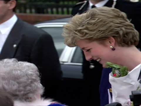 Exterior shots of Princess Diana meeting members of public and being presented with bouquets of flowers as she speaks to people in crowd Princess...