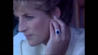 Exterior shots of Princess Diana Princess of Wales sitting down watching a live performance from dancers with shots of her oval blue Ceylon sapphire...
