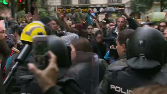 Exterior shots of proindependence supporters on the streets of Barcelona chanting in defiance of the Madrid government with a cordon of riot police...