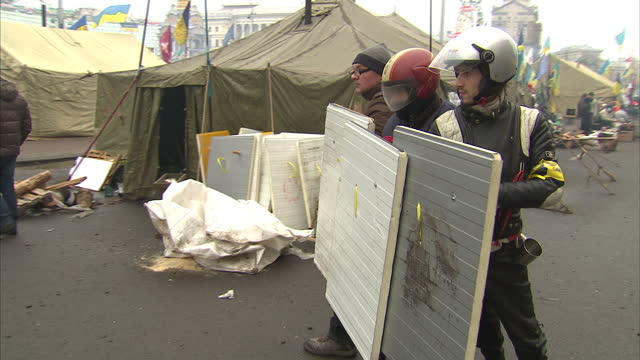Exterior shots of protesters learning how to defend themselves and disarm riot police with makeshift riot shields at a proEurope protest camp in...