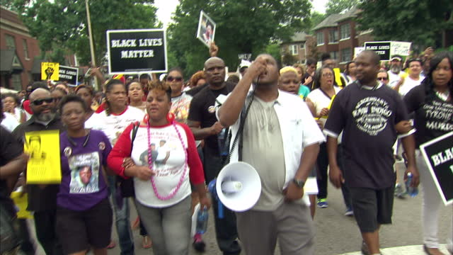 Exterior shots of protesters marching through the streets of Ferguson to mark the anniversary of Michael Brown's death carrying banners calling for...