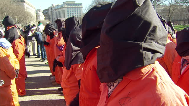 Exterior shots of protesters outside the White House many clad in orange jump suits and hoods holding protest banners calling for the closure of the...