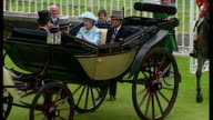 Exterior shots of Queen Elizabeth II and Prince Philip arriving at Royal Ascot in horse drawn carriage with Queen wearing turquoise outfit with...
