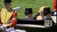 Exterior shots of Queen Elizabeth II arriving wearing apricot coloured outfit with matching hat being carried in horse drawn carriage with Prince...