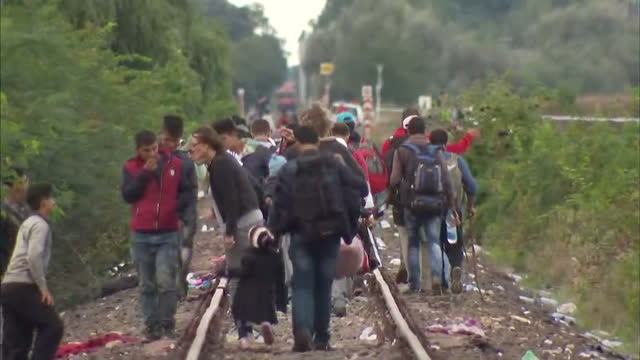 Exterior shots of refugees walking along train tracks with their belongings and moving their tents on September 7 2015 in Roszke Hungary