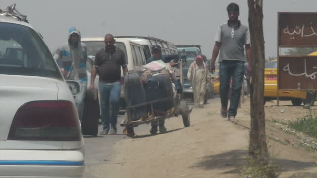 Exterior shots of refugees walking past traffic with belongings and young children on May 21 2015 in Anbar Iraq