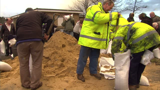 Exterior shots of residents and Environment Agency workers filling sandbags in Great Yarmouth in preparation against a large tidal surge High winds...
