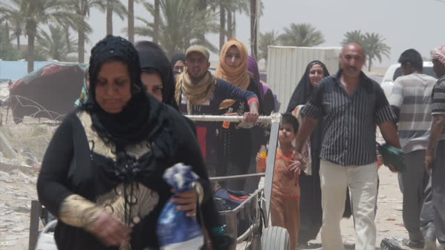 Exterior shots of residents crossing the border in Anbar province with belongings and families and armed Iraqi military soldiers patrolling the...