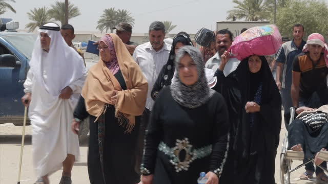 Exterior shots of residents crossing the border in Anbar province with belongings and families on May 21 2015 in Anbar Iraq