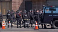 Exterior shots of riot police in a Baltimore street the day after an outbreak of civil unrest as volunteers clean up debris next to burnt out shops...