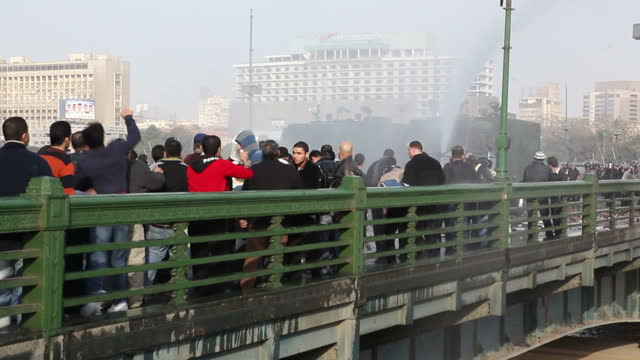Exterior shots of riot police spraying protesters with water canons as they cross Qasr AlNil Bridge on January 28 2011 in Cairo Egypt