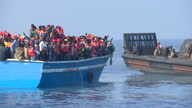 Exterior shots of Royal Navy sailors from HMS Bulwark on a rescue vessel helping a boat full of migrants at sea on June 08 2015 in Catania Italy