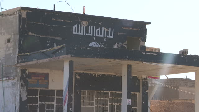 Exterior shots of rubble and damaged buildings in a town formerly occupied by Islamic State and road signs pointing towards Raqqa and Tal Abiad>> on...